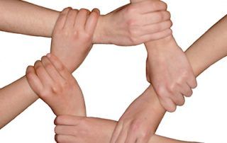 Seven hands holding wrists to make a circle